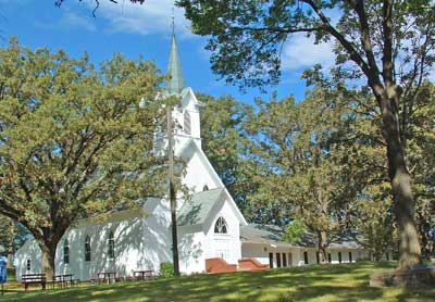A photo of the Nora UU church in the summer.