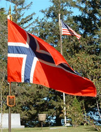A picture of an American and Norwegian flag on the hill near the church.