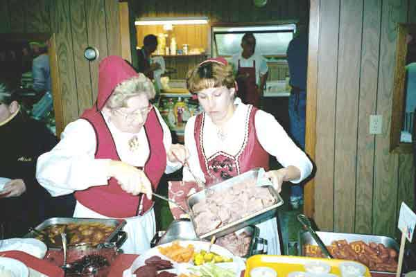 Two women from our church in Norwegian costumes working at the smorgasbord.